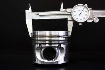 Piston isolated on black background with measuring tool