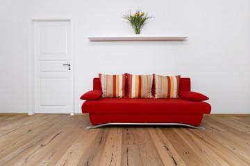 Rote Couch mit bunten Kissen