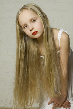 Young girl fashion model with long blond hair