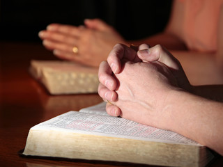 Man and Woman Praying with Holy Bibles