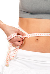 Athletic fit slim woman measuring her waist