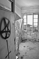 satanic symbols on the door of an abandoned house