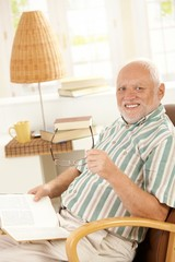 Happy pensioner reading at home