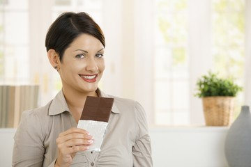 Portrait of excited woman eating chocolate