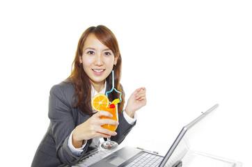 ジュースを飲みながら休憩している笑顔のオフィスレディー