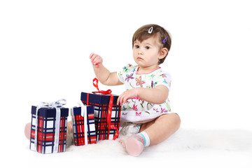 little girl sits with three gift boxes.isolated