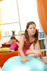 Young girl climbing on gym ball