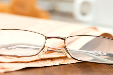 Eyeglasses on the newspaper on a wooden table