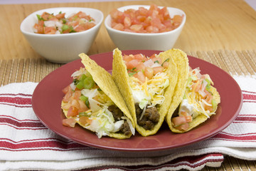 three crunchy tacos on a red plate