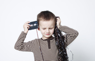 Portrait of cute boy playing with old tapes