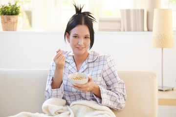 Girl in pyjama having cereal breakfast on couch