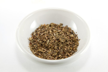 Pile of dried oregano leaves in a bowl on a white background