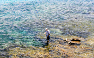 Man fishing in clear blue sea