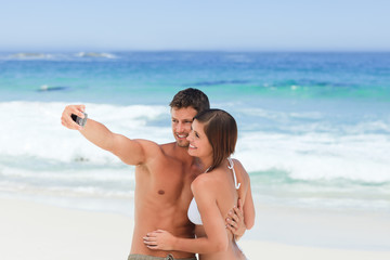 Lovers with their camera at the beach