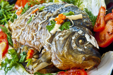 fried fish with fresh herbs, tomatoes.