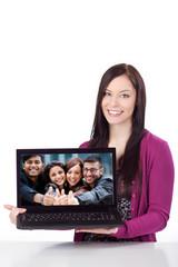 junge frau zeigt foto ihrer freunde am laptop