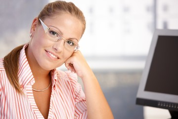 Portrait of young woman working in office smiling