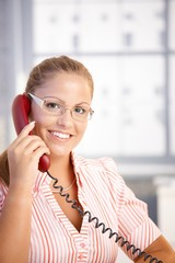 Pretty receptionist working talking on phone