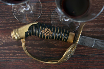 Age-old sword and glasses with wine on a wooden table