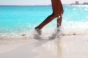 Woman legs walking splashing beach aqua water