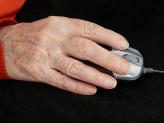 Senior lady hand using computer mouse
