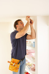Electrician Installing Light Fitting In Home