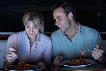 Couple Enjoying Meal Whilst Watching TV