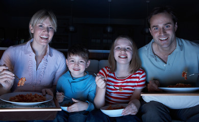 Family Enjoying Meal Whilst Watching TV