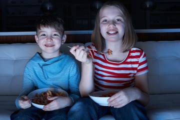 Children Enjoying Meal Whilst Watching TV