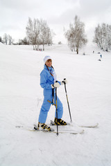 The young girl in sportswear costs on mountain skiing