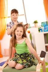 Young girls having fun combing hair