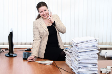Young woman in office interior calling by telephone