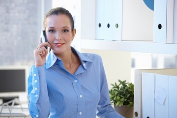 Smiling young businesswoman on call