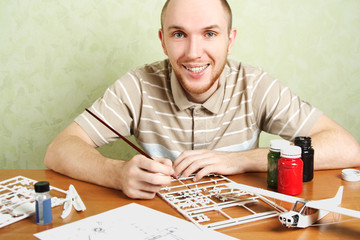 man assembling plastic airplane model and painting pieces, smili
