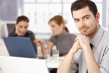 Portrait of young man sitting at meeting table