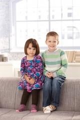 Smiling children sitting on sofa
