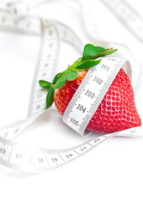 big juicy red ripe strawberries and measure tape isolated on whi