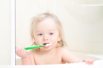 Adorable baby brushing teeth sitting in shower