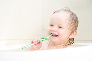 Adorable smiling baby brushing teeth sitting in shower