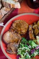 Arista di maiale con contorno di patate e insalata