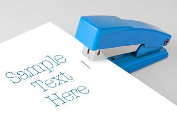 blue stapler lies on a white background