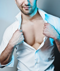Sexy Male Model Unbuttoning His White Shirt