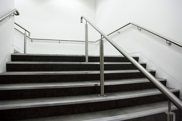Fototapeten Treppe wide staircase with chrome handrails and gray steps, white walls