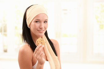 Happy woman in snood holding cookie