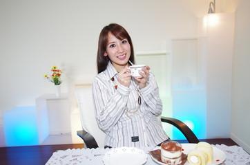 リビングでコーヒーを飲んでいる笑顔の女性