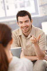 Portrait of happy man chatting with woman at home
