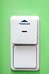 hotel card holder on green wall and light switch
