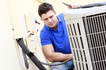 Technician inspects an AC unit