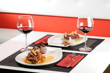 tavola apparecchiata con primi piatti e vino