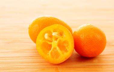 Poster Plakjes fruit kumquat on wooden surface